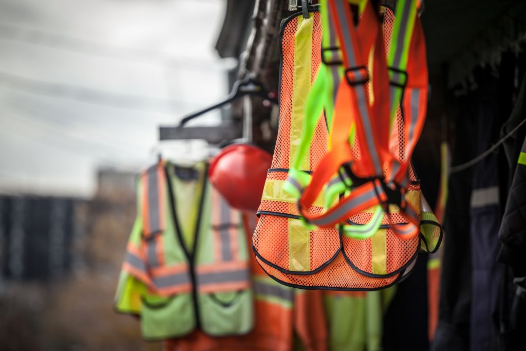 Picture of PPE, or personal protective devices, for sale in a shop, haning. Yellow and Orange vests, harnesses and helmets are visible