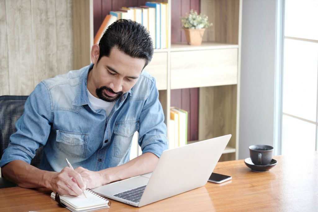Owner Business or Entrepreneur using a laptop for working and writing work schedules in the notebook while sitting at the desk in his home.