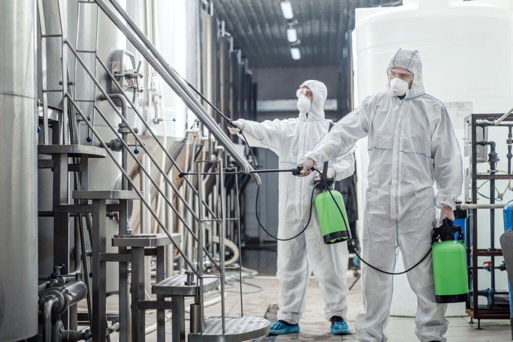 Sanitation at factory of craft beer. Guys in protective suits disinfect at plant