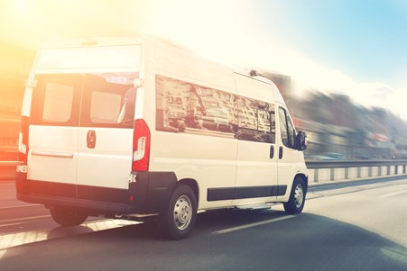 white van driving with sun the background