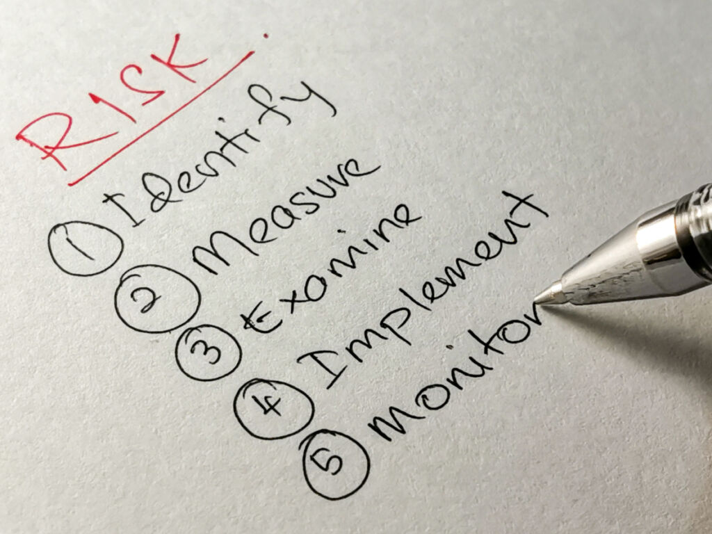 list of 5 with close up of a pen writing, list of risk